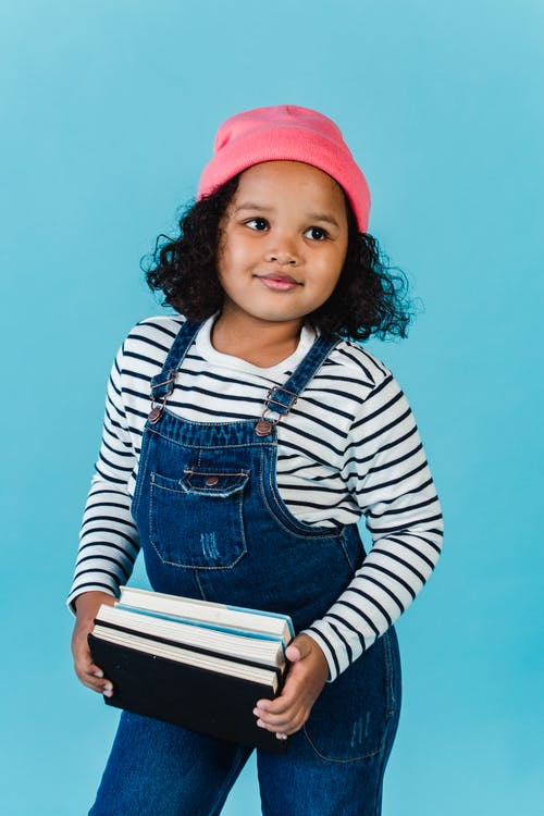 Positive little African American girl wearing hat looking away while standing on blue background with stack of books in hands