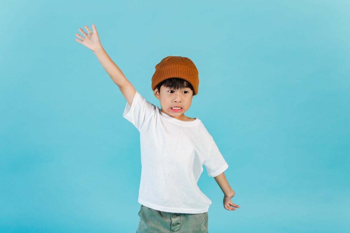 Astonished stylish Asian boy wearing hat and white t shirt looking away while standing with outstretched arms in light studio