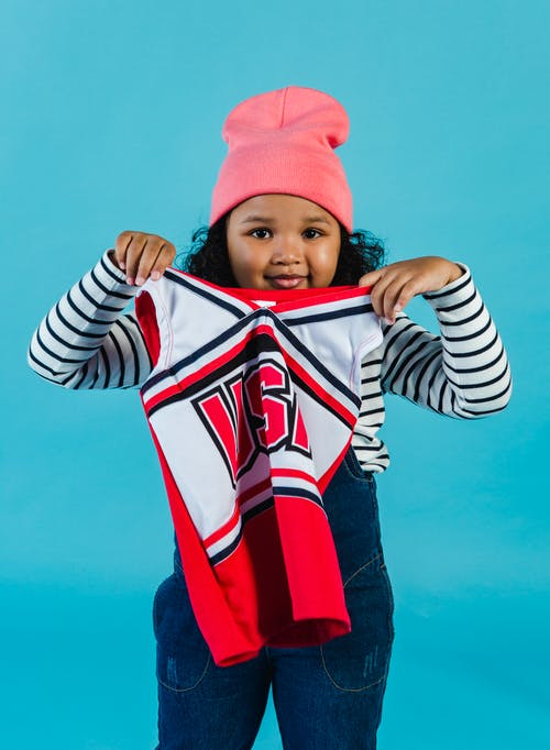 Smiling African American kid in hat looking at camera while standing on blue background with red cheerleader top in hands