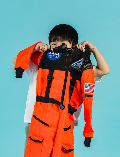 Anonymous Asian kid with spacesuit in hands