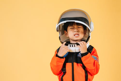 Asian kid wearing astronaut helmet