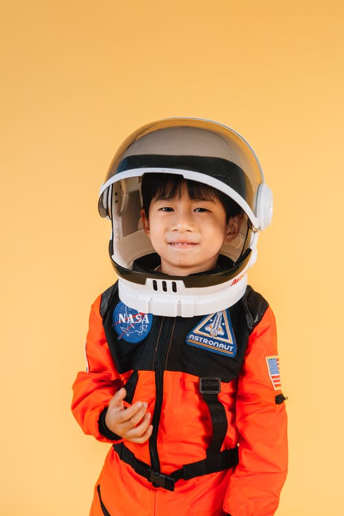 Cheerful Asian kid wearing helmet and orange astronaut suit looking at camera while standing on yellow background in modern studio