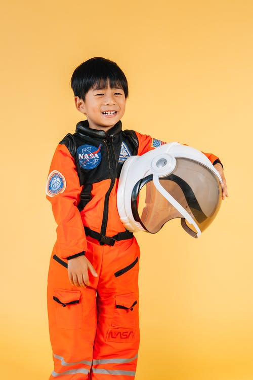 Cheerful Asian kid wearing orange astronaut suit smiling and looking away while standing on yellow background with helmet in hands