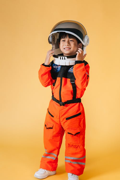 Positive Asian kid wearing orange astronaut costume and helmet smiling and looking away while standing on yellow background in studio