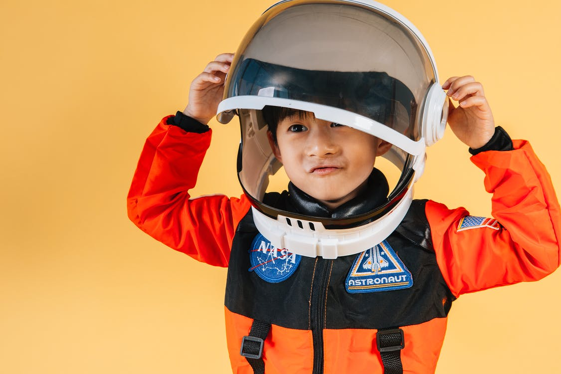 Positive Asian kid wearing cosmonaut helmet
