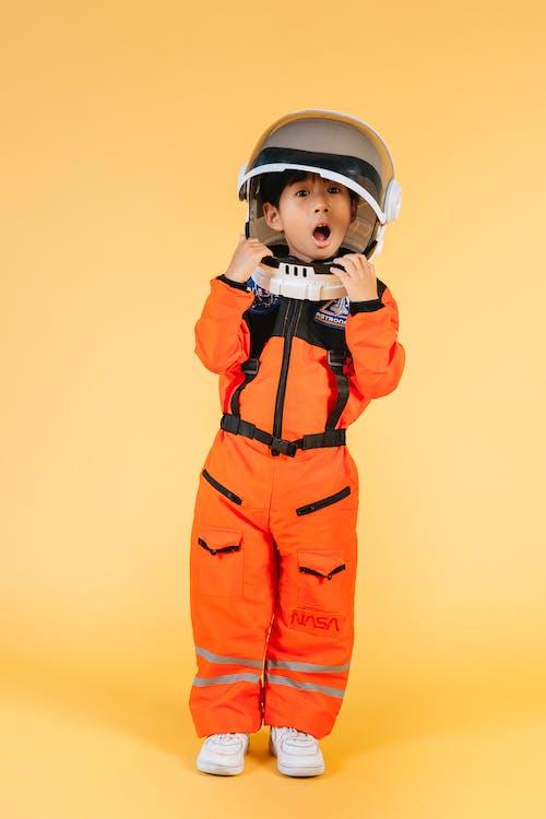 Garçon En Veste Zippée Orange Et Noire Portant Un Casque