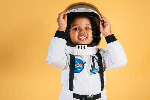Smiling little African American girl in white space suit looking at camera touching helmet on orange background