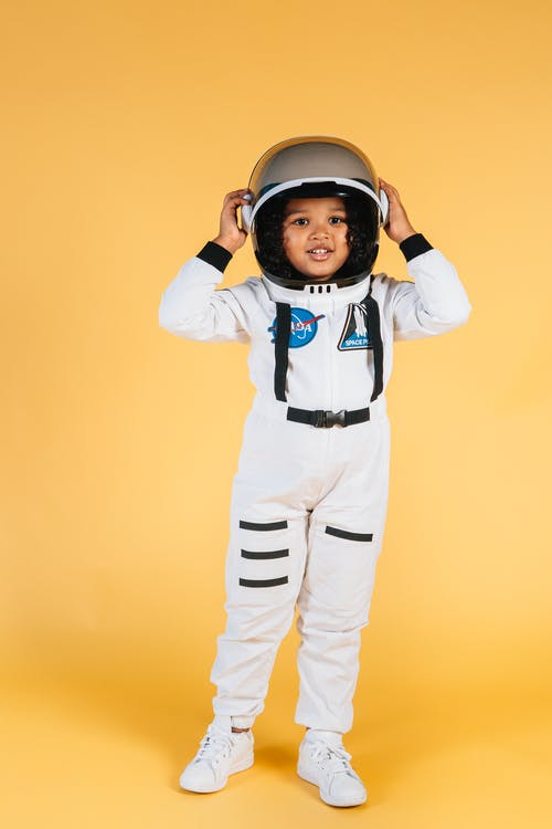 Full body cute little kid wearing white space suit  and looking at camera touching helmet on orange background