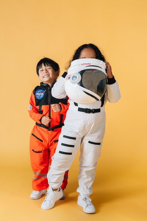 Multiethnic children in astronaut costumes against yellow background in studio