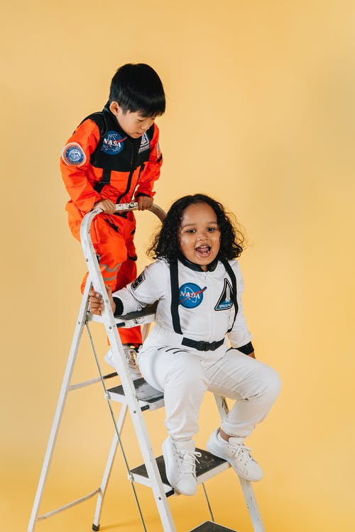 Playful diverse children in colorful astronaut costumes on metal ladder in studio against yellow background