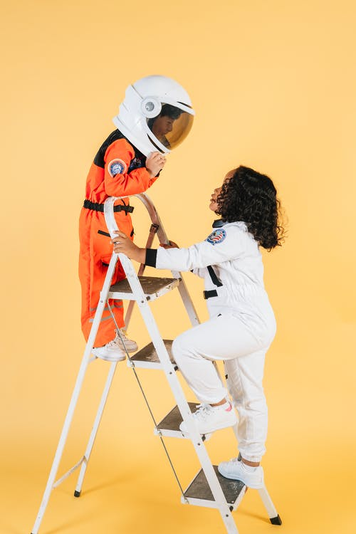 Children in astronaut costumes playing in studio with yellow walls