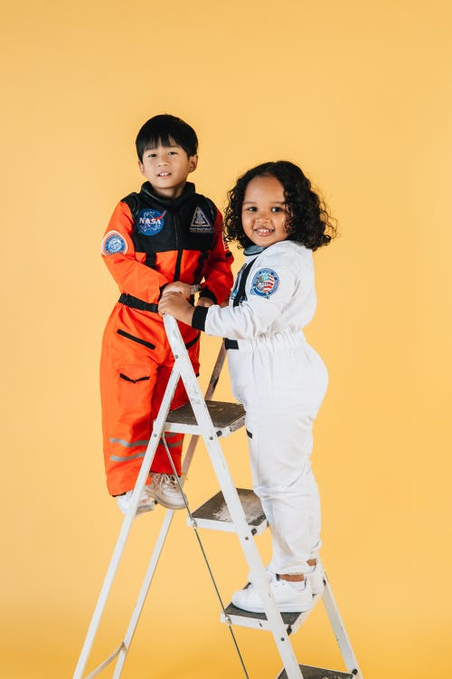 Smiling multiracial children in astronaut costumes standing on ladder and looking away against yellow background in studio
