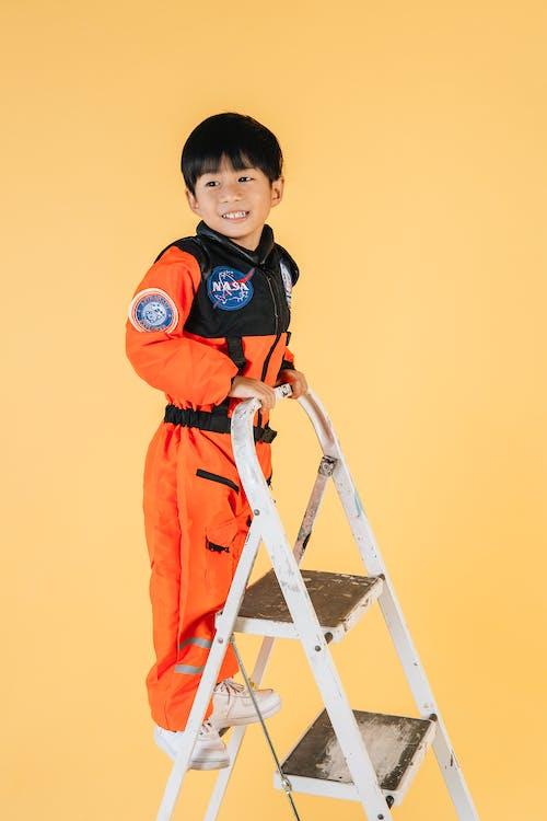 Smiling Asian boy in astronaut costume in studio