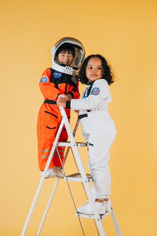 Full length of positive multiethnic children in colorful astronaut costumes standing on top of ladder against yellow background in studio