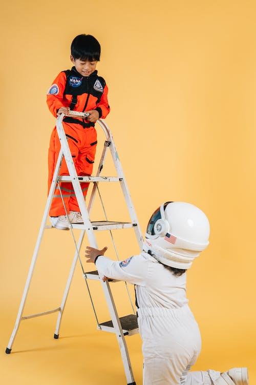 Мужчина в белой рубашке с длинным рукавом и оранжевом шлеме стоит на лестнице