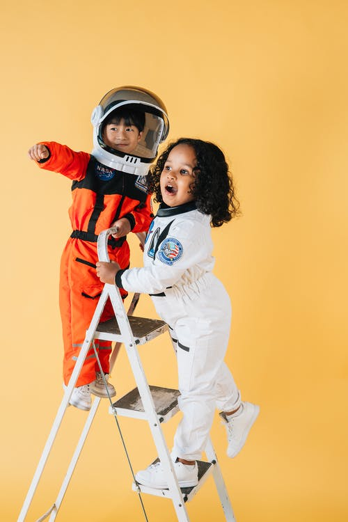 Cheerful multiracial children in astronaut costumes standing on ladder in studio against yellow background and looking away
