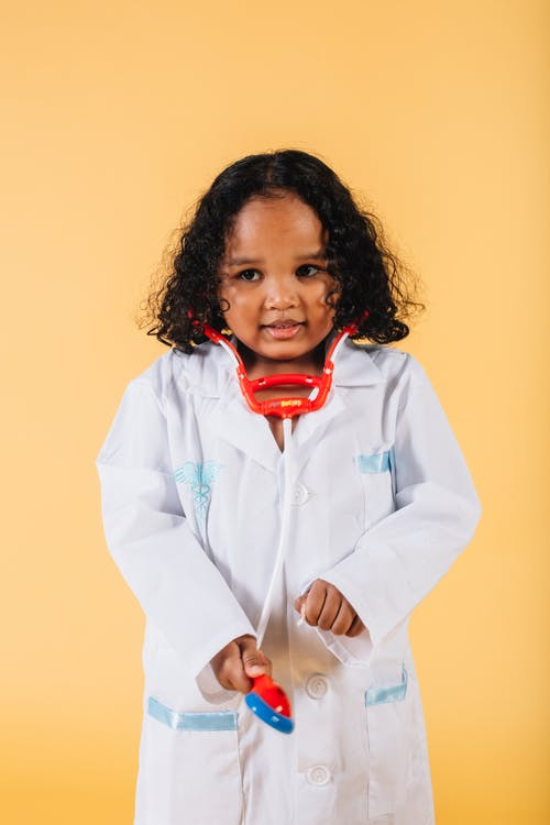 Positive little black girl wearing medical uniform against yellow background
