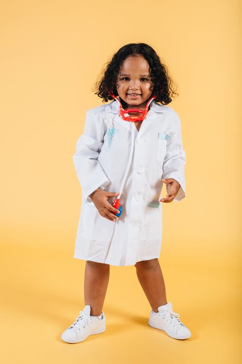 Smiling black girl in medical costume standing in studio with yellow background
