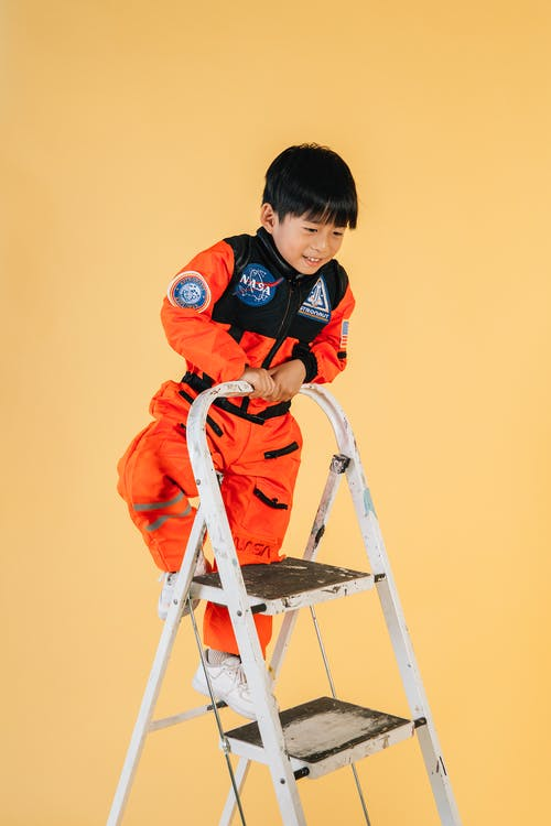 Playful Asian boy in orange astronaut costume climbing up ladder in studio against yellow background