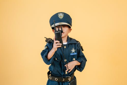 Asian boy in police uniform against yellow background