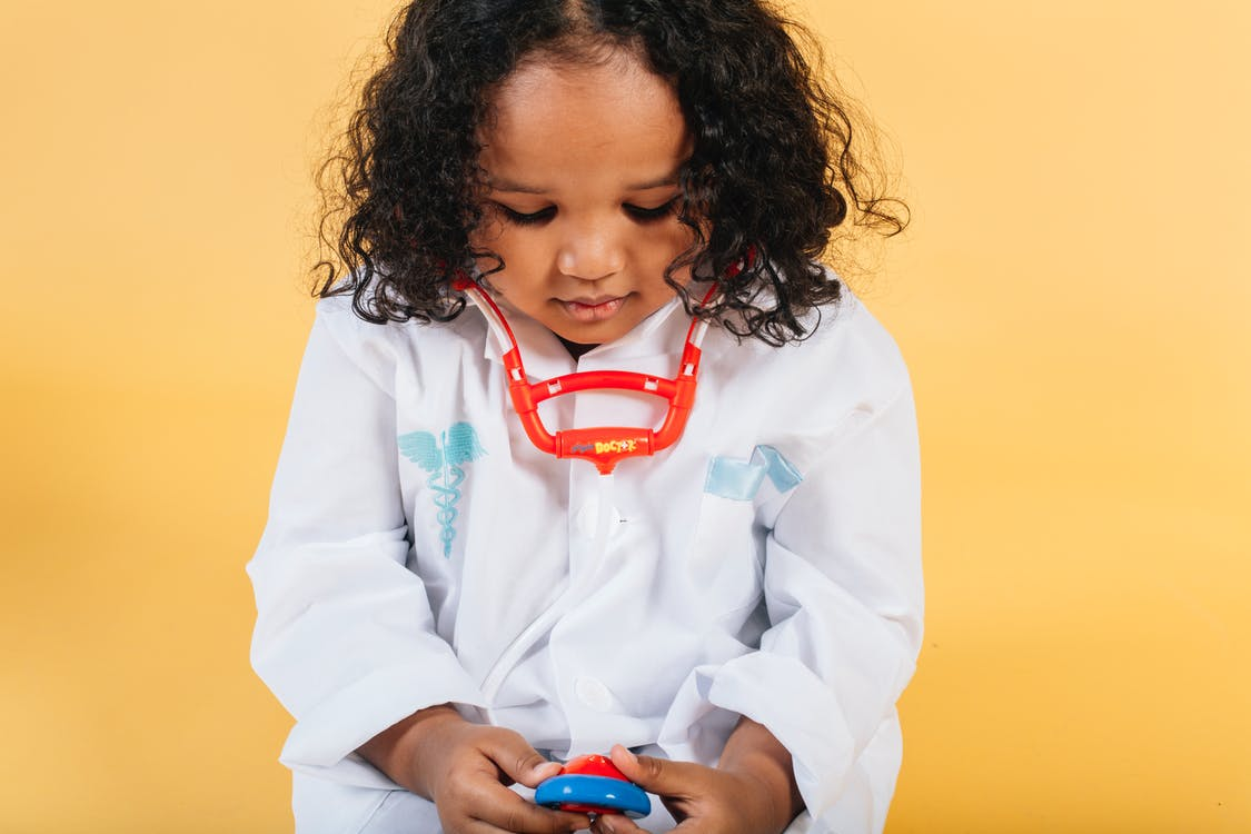 Tranquil little African American girl with curly hair in medical costume and stethoscope looking down against yellow background in studio