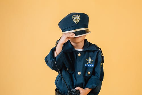 Unrecognizable child in police uniform standing in studio with transceiver in hand and pulling cap over face on yellow background