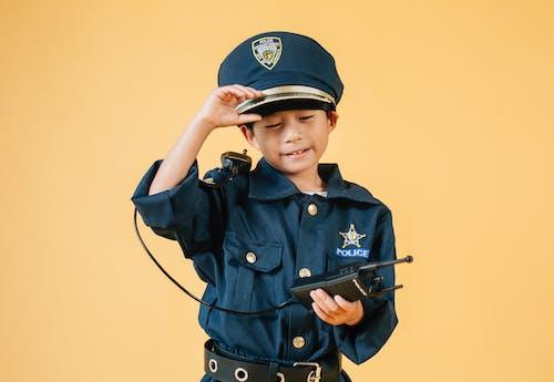Anak Laki Laki Berkancing Biru Mengenakan Topi Hitam