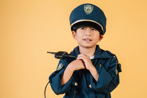 Pleasant Asian boy in police uniform and cap looking away while standing with hands near chest in studio on yellow background