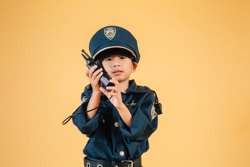 Serious Asian kid in police uniform with transceiver