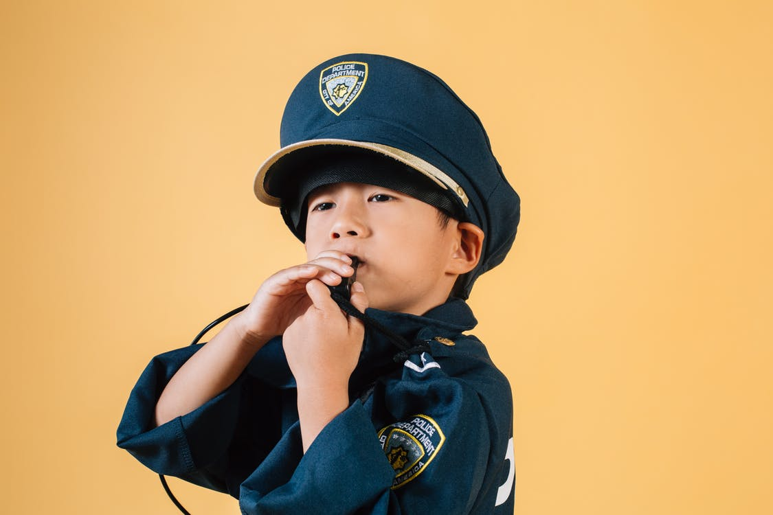 Confident Asian boy in police uniform holding in hands whistle and blowing while standing in studio on yellow background and looking away