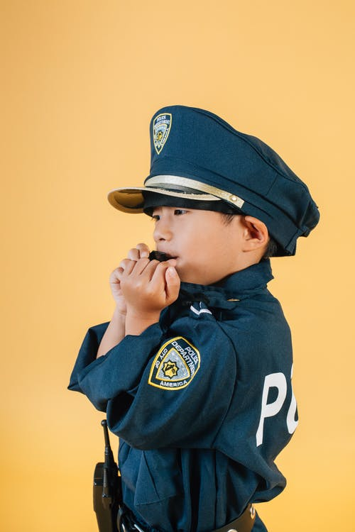 Asian kid in police uniform blowing whistle in studio