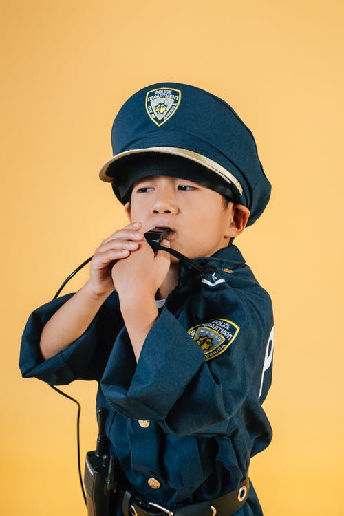 Focused ethnic kid in police uniform costume blowing whistle while standing in photo studio on yellow background and looking away