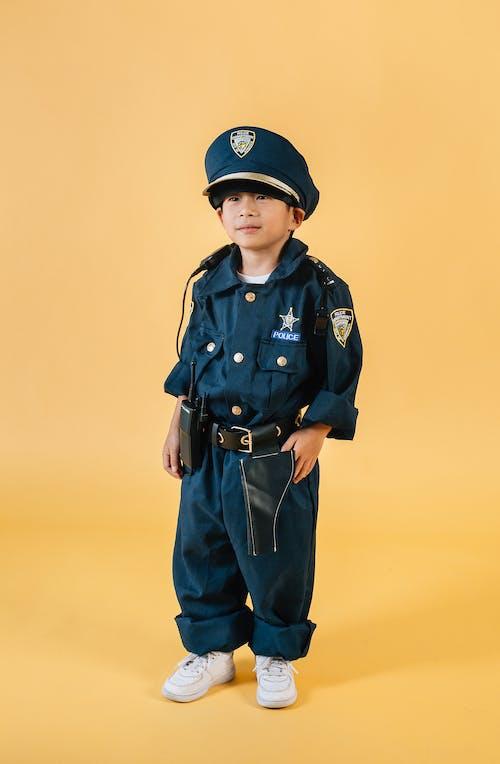 Asian child in policeman costume in studio