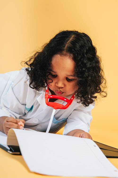 Focused curly African American girl in doctor costume with toy stethoscope taking notes in medical card while lying on floor in studio on yellow background