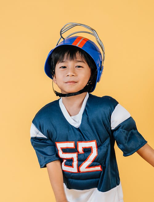 Satisfied ethnic child in American football player costume and helmet