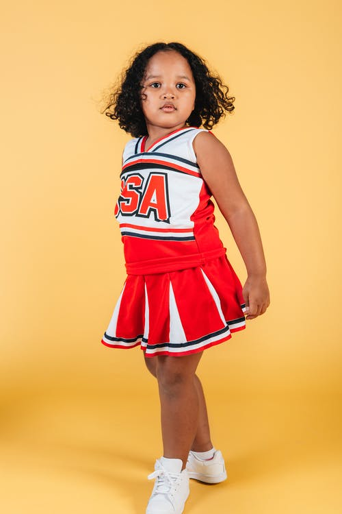 Serious curly black girl in cheerleader costume and sneakers standing in confident pose with round chest on yellow background in studio
