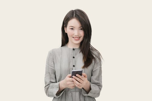 Woman in Gray Button-up Long-sleeved Dress Holding Black Smartphone