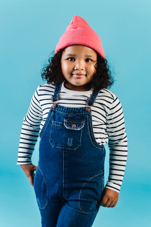 Smiling curly haired black girl in denim overall and pink knitted hat standing on blue background in studio and looking at camera
