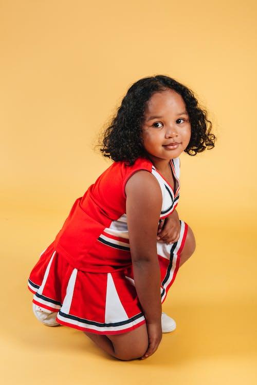 Satisfied black female child in cheerleader costume