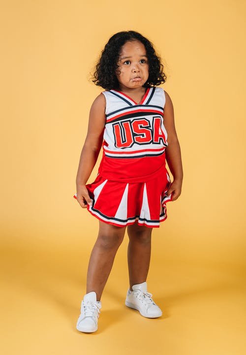 Full body African American curly female kid in cheerleader costume standing on yellow background with offended face in studio and looking away