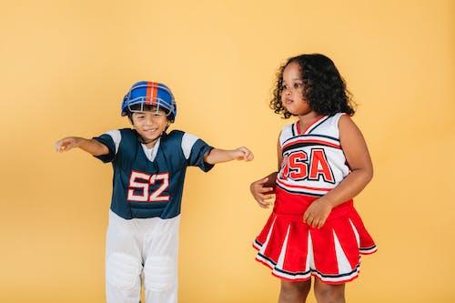 Cheerful multiracial kids wearing football player and cheerleader costumes