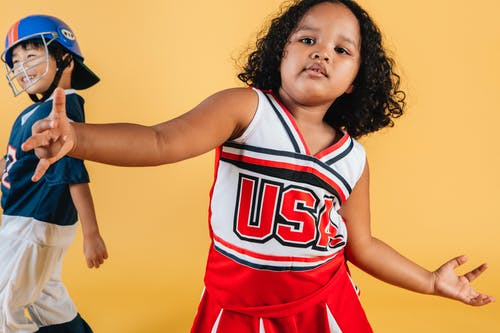 Cute African American girl wearing cheerleader uniform dancing on yellow background near cheerful Asian boy in helmet and football player costume