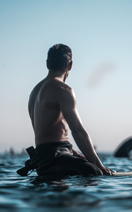 Back view of shirtless male with muscular torso sitting on surfboard and looking at sky