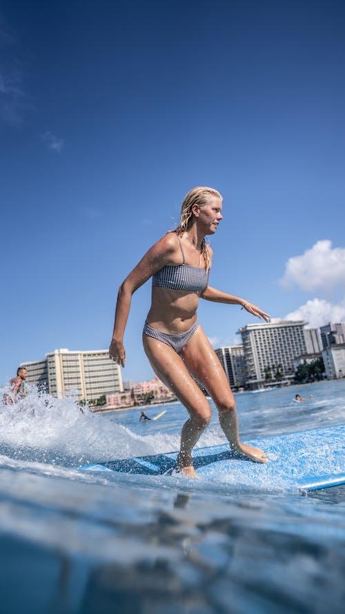 Woman splashing water on surfboard near resort