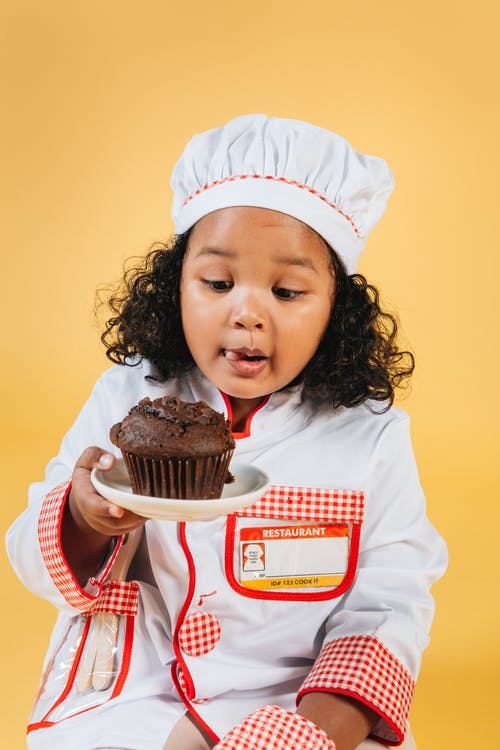 Excited African American girl wearing chef uniform and hat sitting on yellow background and licking lips while looking at tasty chocolate muffin