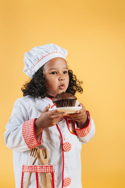 Adorable black girl cook standing with chocolate cupcake