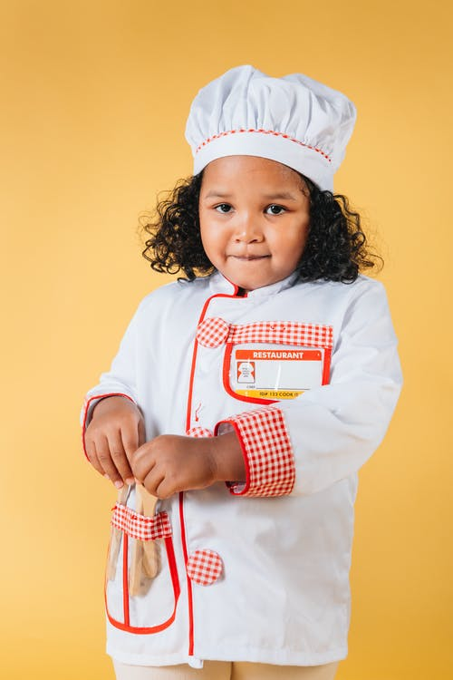 Content little African American girl wearing chef uniform and hat standing against brown background in studio
