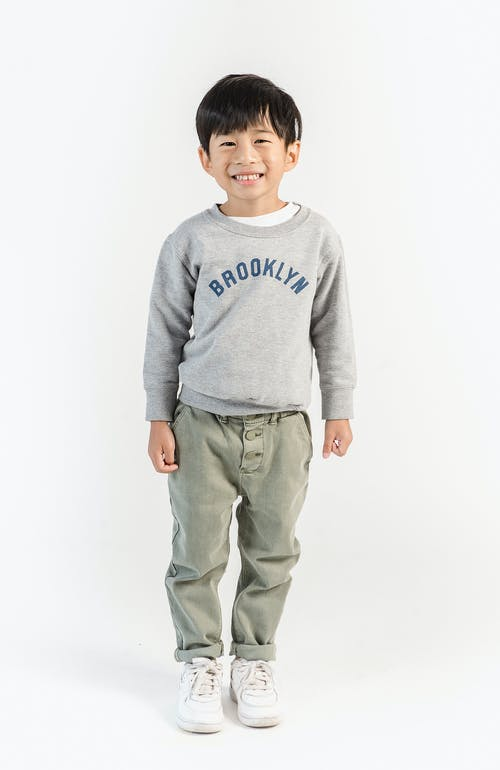 Full body joyful little Asian boy in cool outfit standing against white wall and looking at camera with happy smile