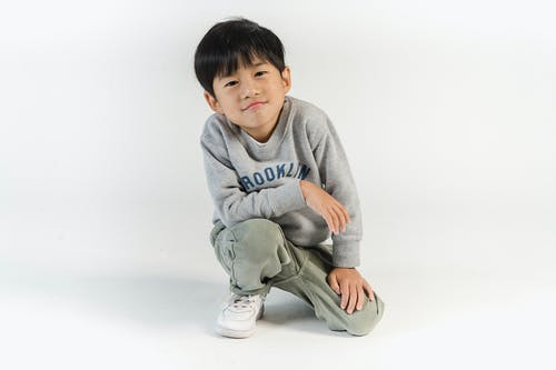 Content little Asian boy in stylish outfit sitting on haunches and looking at camera confidently during photo shoot in light studio