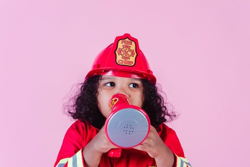 Cute little African American girl wearing bright firefighter costume and helmet and talking in toy loudspeaker while playing in light studio and looking away